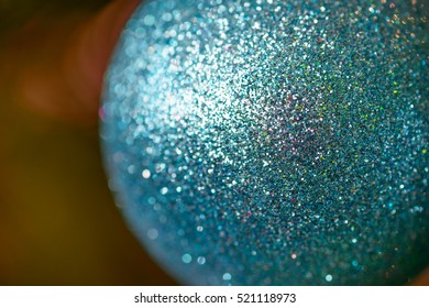 Closeup of turquoise glittering christmas ball hanging on christmas tree, low depth of focus