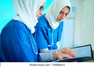 Close-up of two arabic female doctors dressed in blue uniform and white hijab sitting in a hospital reading a medical report