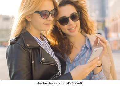 Closeup of two attractive young women using mobile phone outdoors. Travel concept.