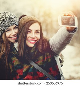 Closeup of two beautiful Caucasian teenage girls with knit beanie hats taking a selfie with smartphone outdoors in winter. Square format images, retouched, instagram look, filter applied.