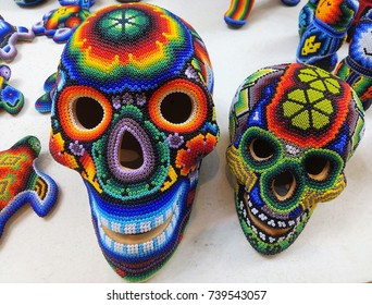Close-up of two beautiful colorful skulls made from beads – example of traditional huicholes art typical for Huichol People, native Americans / Indians living in some Mexican states