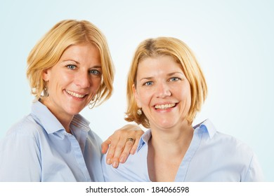 Close-up of two beautiful women looking at the camera. Studio shot isolated on light blue background
