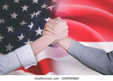 Closeup of two business people shaking hands after deal business with America and Indonesia flag in the background