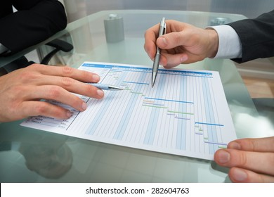 Close-up Of Two Businessman With Gantt Diagram At Desk