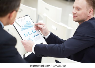 Close-up of two businessmen discussing paper