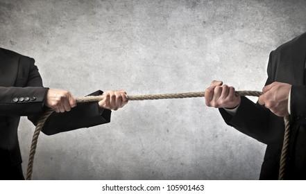 Closeup of two businessmen playing tug of war