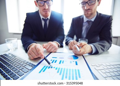 Close-up of two businessmen pointing at chart in document
