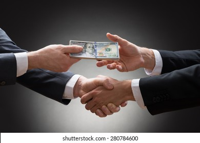Close-up Of Two Businessmen Shaking Hands And Receiving Banknote
