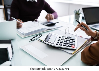Close-up Of Two Businesspeople Calculating Financial Statement At Desk