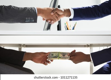 Close-up Of Two Businesspeople Shaking Hand And Taking Bribe Under Wooden Table