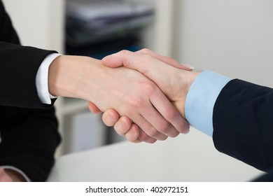 Close-up Of Two Businesspeople Shaking Hand In Office