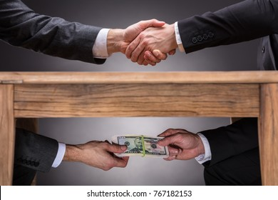 Close-up Of Two Businesspeople Shaking Hand And Taking Bribe Under Wooden Table On Grey Background