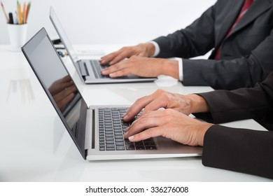 Close-up Of Two Businesspeople Using Laptop At Desk