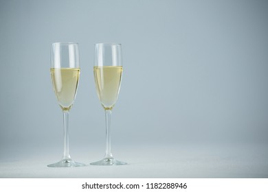 Close-up of two champagne flutes against white background