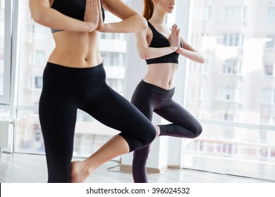 Closeup of two concentrated young women standing and doing balancing pose in yoga studio