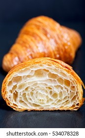 close-up of two croissants, one cut in half with inside texture visible, delicious french pastry