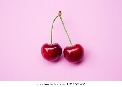 closeup of two delicious cherries on pink background