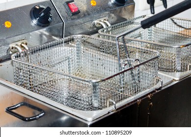 Closeup of two empty deep dirty fryers with shallow depth of field