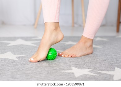 close-up two feet with a pedicure of a young woman, one foot stands on a green spiky massage ball on a carpet in a home interior.