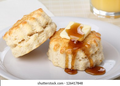 Closeup of two flaky biscuits with butter and honey on top