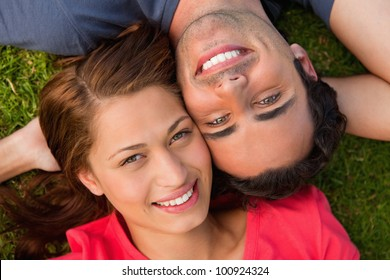 Close-up of two friends smiling while looking towards they sky as they lie head to shoulder with an arm behind their head on the grass