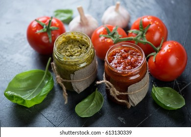Close-up of two glass jars with red pesto and basil pesto with cooking ingredients, selective focus