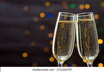 Close-up of two glasses with bubbly champagne tilted to each other against a background of blurry sparkles. Concept of a romantic evening and dinner in a restaurant. Place for advertising