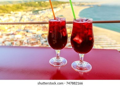 Closeup of two glasses of Sangria overlooking Nazare skyline on blurred background.Concept of holiday celebration, vacation and aperitif.Nazare in portugal is a famous tourist resort on Atlantic coast