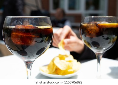 closeup of two glasses with vermouth, a fortified wine served on the rocks with a slice of orange, and a bowl with potato chips, eaten traditionally as an appetizer on Sundays in Catalonia, Spain