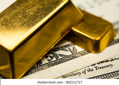 Close-up of two gold ingots and dollar banknotes