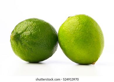 Closeup of two green limes resting on each other on a white background