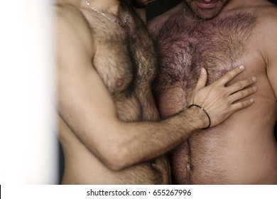 closeup of two hairy naked men holding each other