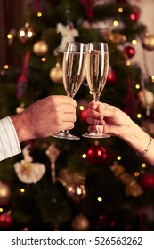 Close-up of two hands with champagne glasses making toast. Two hands clinking champagne glasses over background with decorated Christmas tree