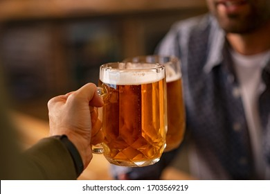 Closeup of two hands clinking beer stein glasses. Toasting with a pint of draft beers on counter at pub. Detail of happy men hands raising toast with cold beer mugs at bar.
