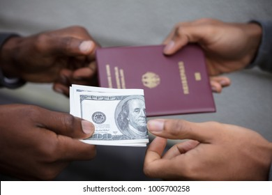 Close-up Of Two Hands Exchanging Passport For Us Dollar Notes