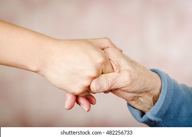 Closeup two hands holding each other appearing to be that of a young and one old person
