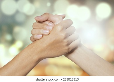 Closeup of two hands joining together, symbolizing to trust each other, shot with a bokeh background