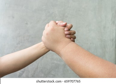 Closeup of two hands joining together by big and little hand, symbolizing to trust each other, arm wrestling