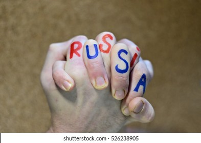 Close-up, two hands locked in fight. On the one of the hand written Russia, on another USA. Wordplay.
