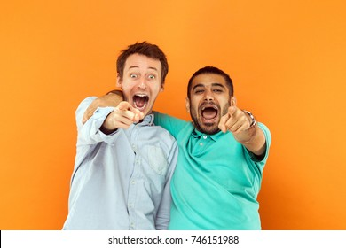 Closeup. Two happiness friends hugging each other, pointing finger  and looking at camera and scream or shout. Studio shot on orange background