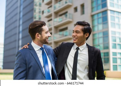 Closeup of Two Happy Colleagues Embracing Outside