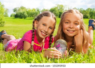 Close-up of two happy little nine years old girls hold jar with butterfly laying in the grass and showing big smile on happy faces