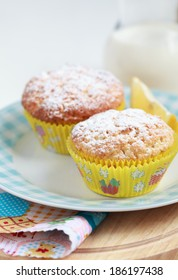 Close-up of two homemade lemon muffins with a jug of milk, selective focus