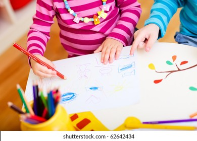 Closeup of two kids drawing with coloring pencils