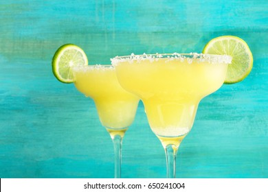 A closeup of two lemon Margarita cocktails with wedges of lime on a vibrant turquoise background with copy space