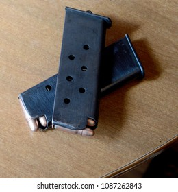 A closeup of two magazine clips from a handgun sitting on the table.