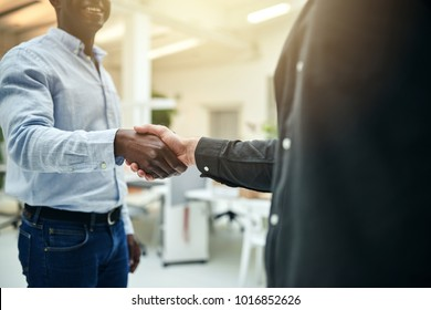 Closeup of two male business colleagues shaking hands together while standing in a modern office