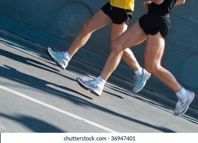 Close-up of two marathon runners with motion blur to accent speed