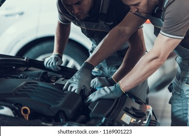 Close-up of Two Mecanics while Fixing Car. Strong Muscular Workers in Uniform and Gloves Repairing Automobile Engine with Opened Hood Posing with Serious Expression. Repair Service Concept