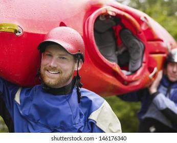 Closeup of two men carrying red kayak to river